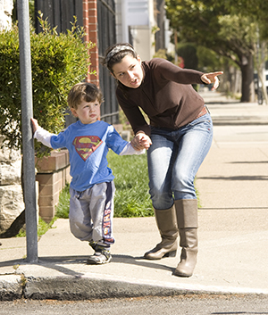 Woman holding toddler boy's hand before crossing street.
